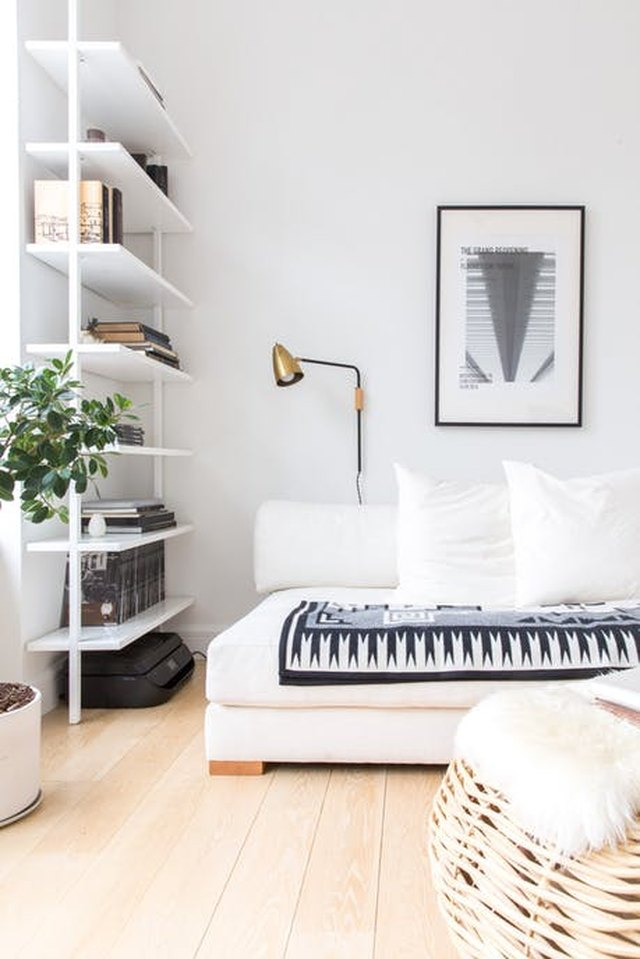 White living room featuring blue and white patterned throw blanket on couch