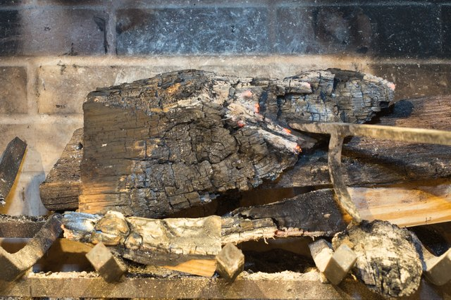 Grab your fireplace poker and gently spread out the wood and embers. A flattened mound will help cool the fire. & How to Put Out a Fire in a Fireplace | Hunker