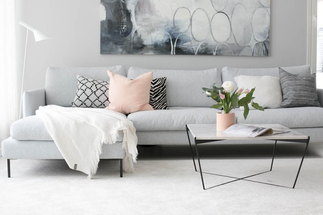A gray couch, cream rug, and pink pillow.