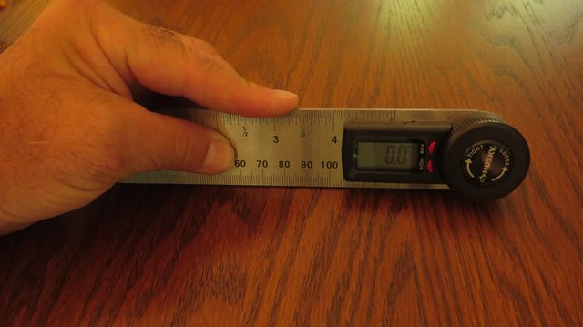 A digital protractor against a table.