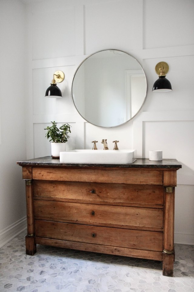 white wall flat panel white wainscoting round mirror and sink vanity