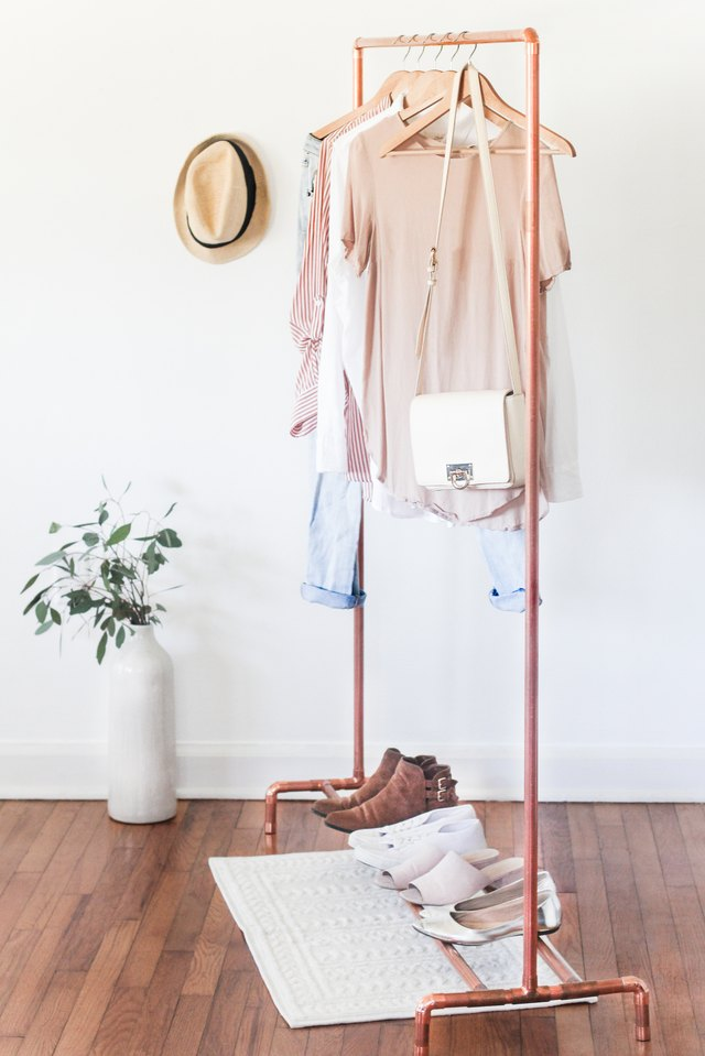 Copper clothing stand with clothes and shoes