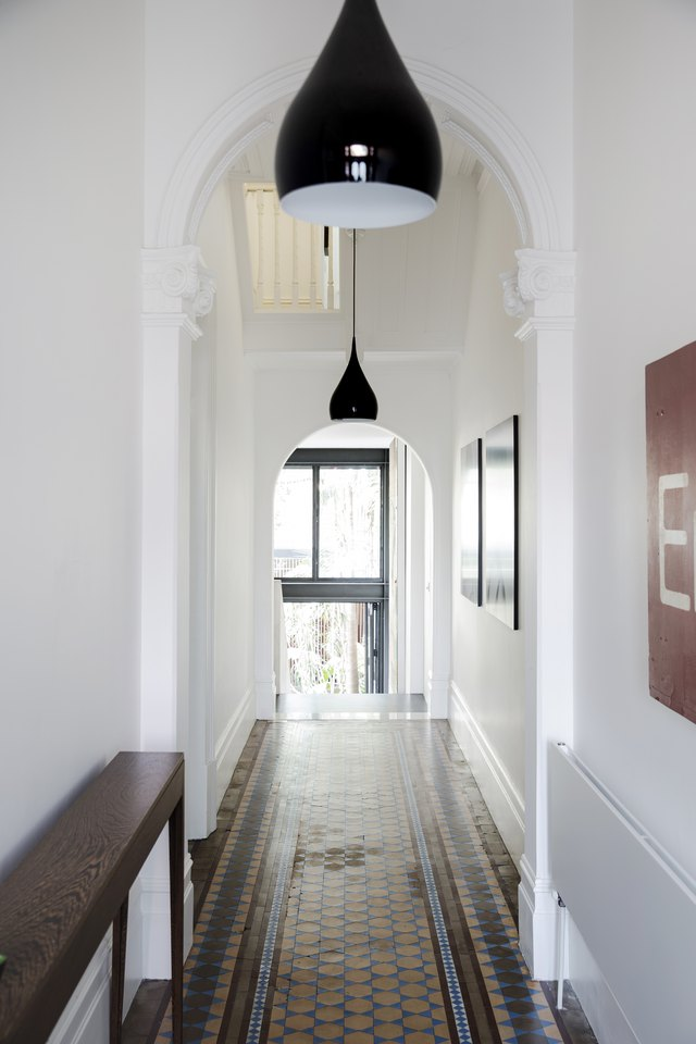 Hallway with tiled floor, white walls and black pendant lights.