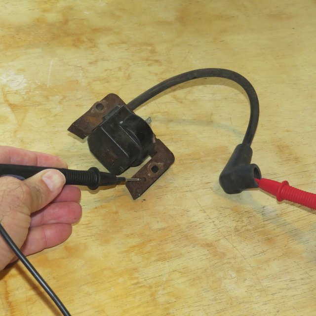 Wire leads testing a lawnmower ignition coil.