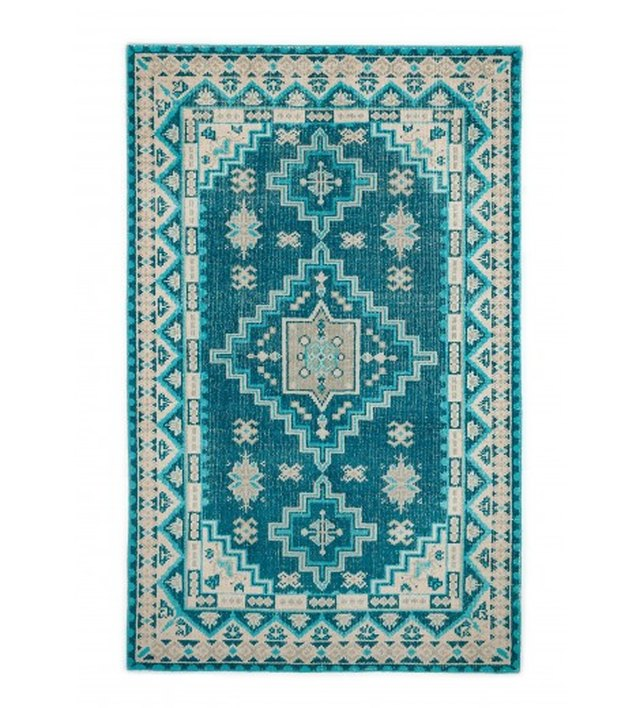 Turquoise area rug with off-white details
