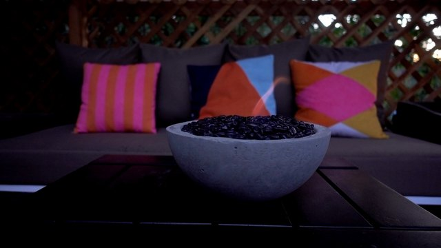 DIY tabletop concrete fire bowl on an outdoor coffee table in the evening.