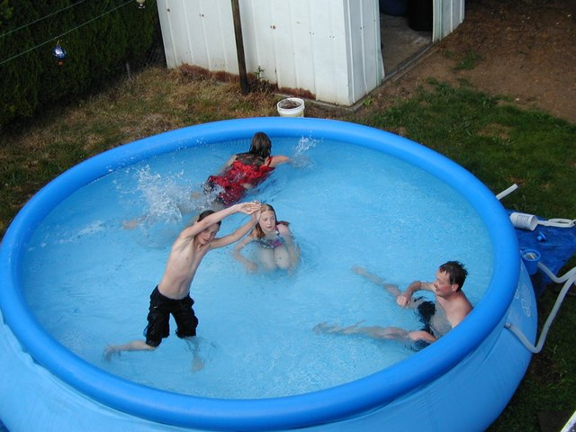 Kids playing in a soft-side above-ground swimming pool.
