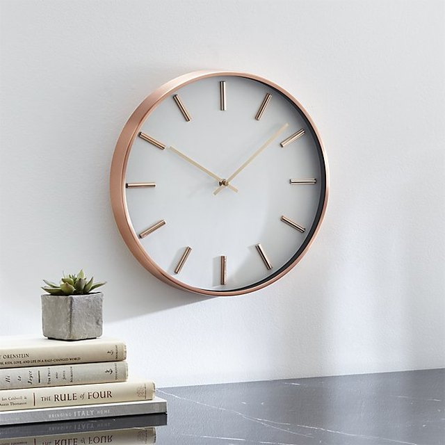 Wall clock with white face and copper frame and copper bars in lieu of numbers
