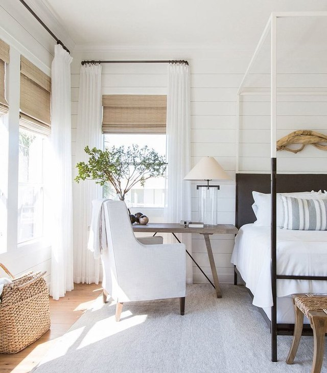 Bedroom featuring white curtains opened around tan woven roman blinds