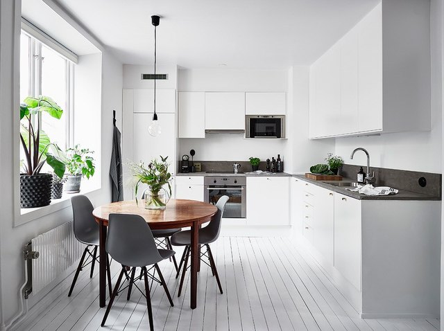 White kitchen with wood circular table and gray mid-century dining chairs