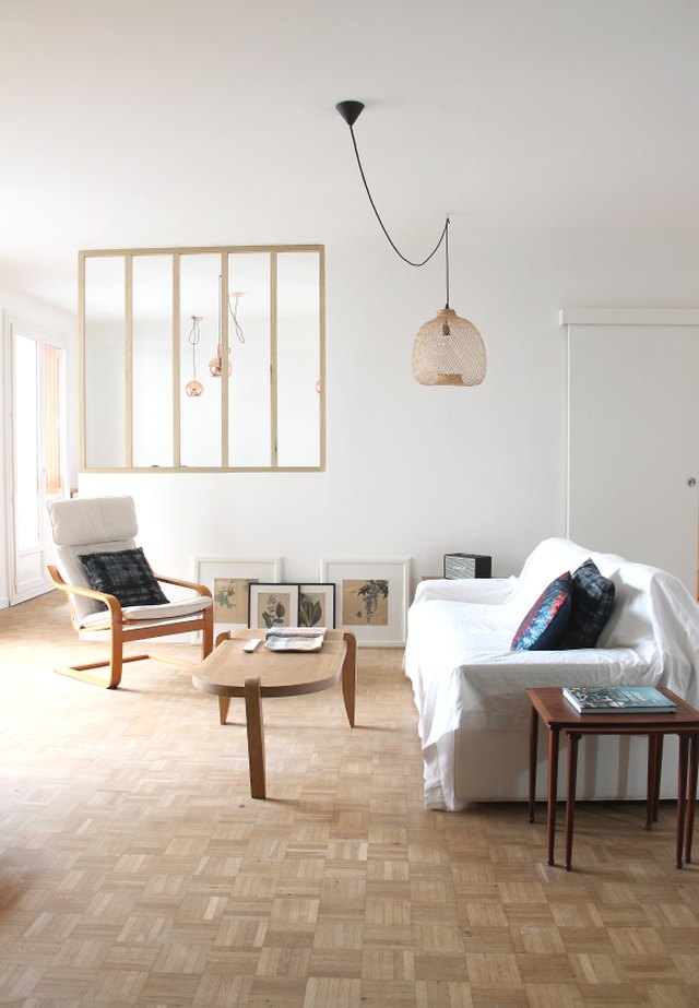 A room with white walls, parquet floors, and sparse decor.