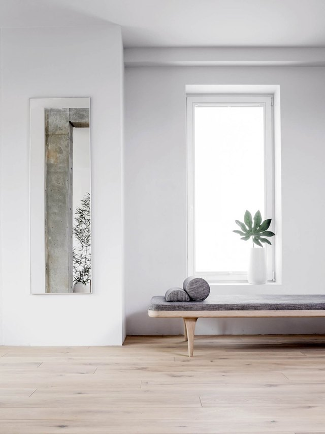 A daybed in front of a tall window with a plant in a white vase on the sill.