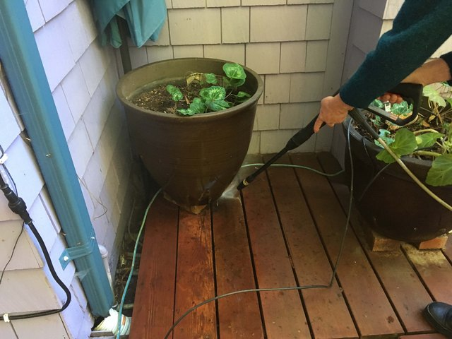 Washing surface dirt from a corner of a deck.