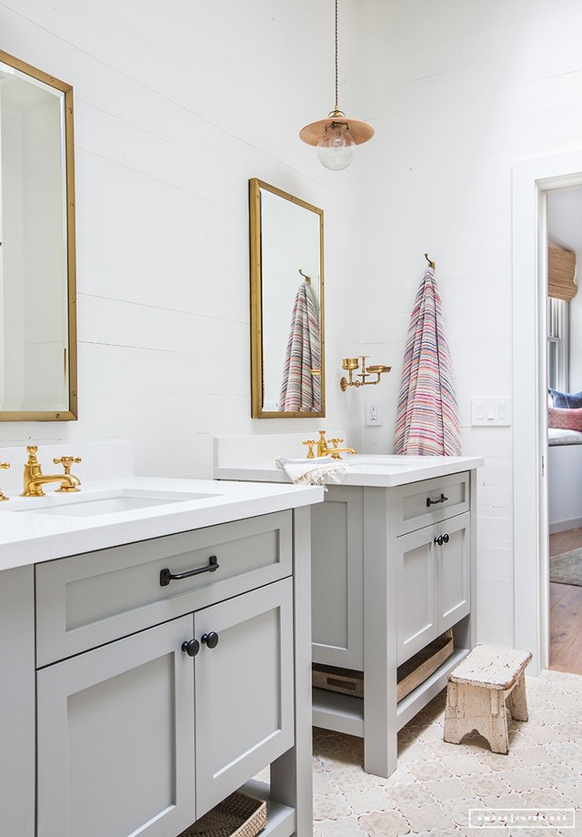 Bathroom with twin sinks featuring brass faucets and black cabinetry hardware