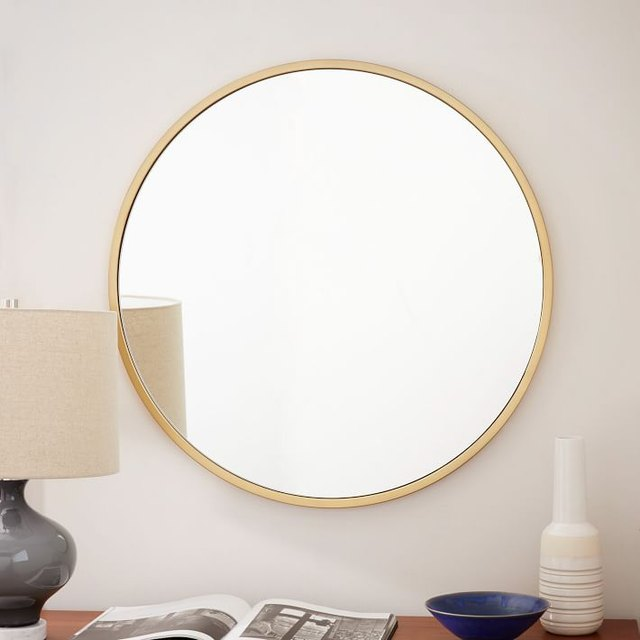 Large round mirror with thin gold metal frame