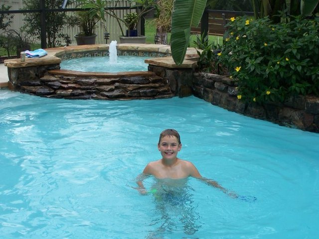 Boy playing in swimming pool.