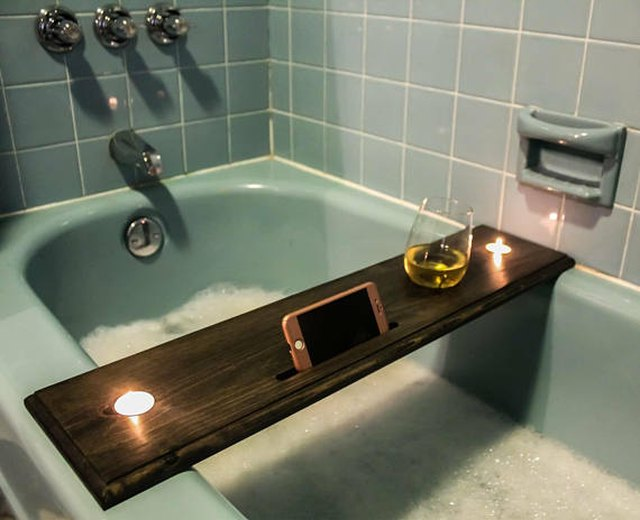 Wooden bathtub tray with designations for phone/tablet, beverages and candles