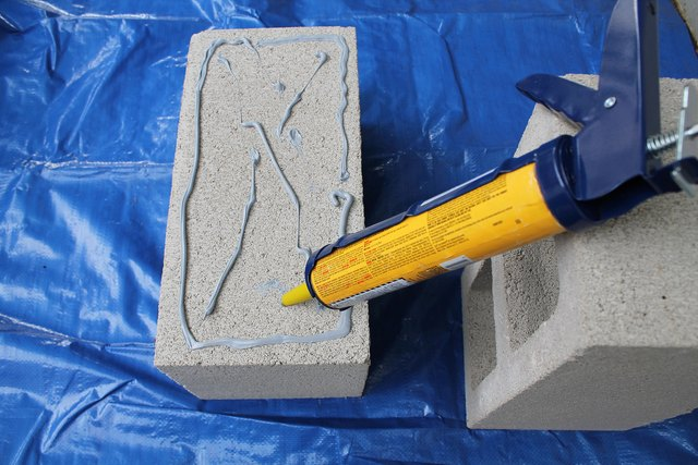Add concrete adhesive to the first block.