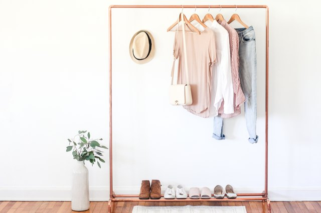 Copper clothing stand styled with clothes and shoes