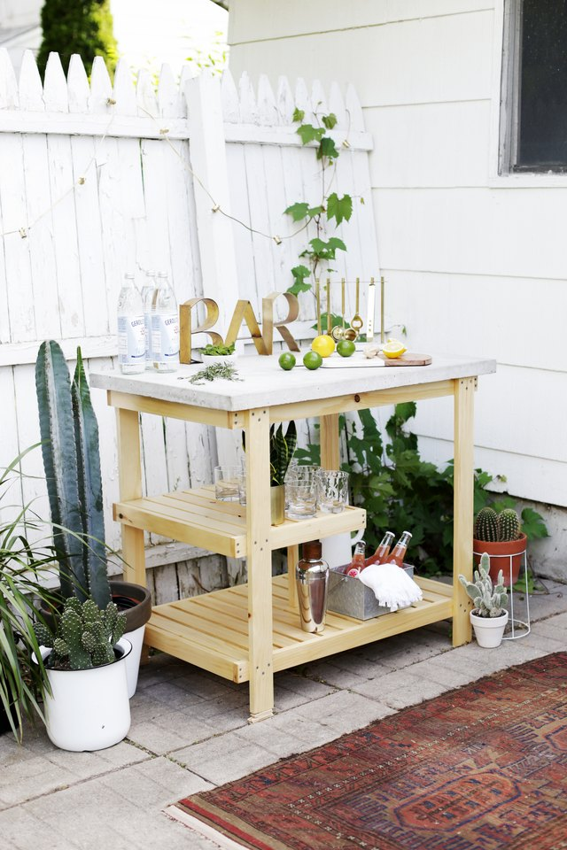 outdoor bar with concrete top and drinks on it.