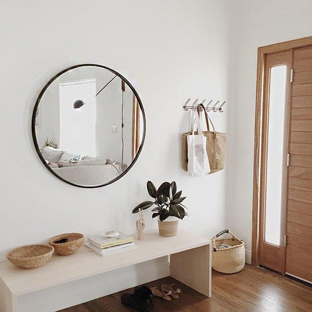 Minimal entryway featuring big round mirror