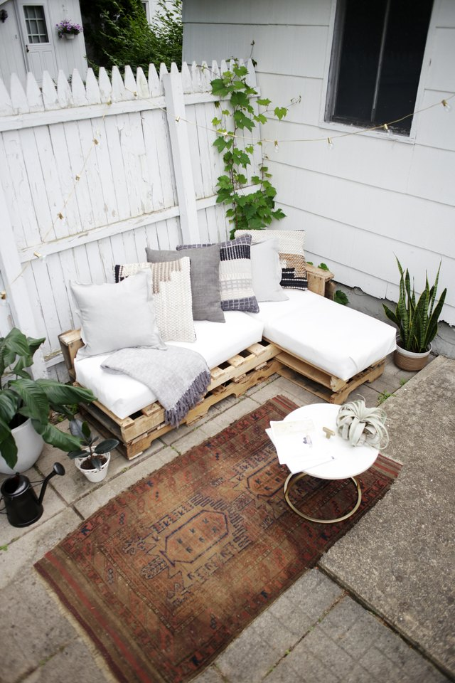 Wood pallet couch on patio with white cushions and throw pillows.