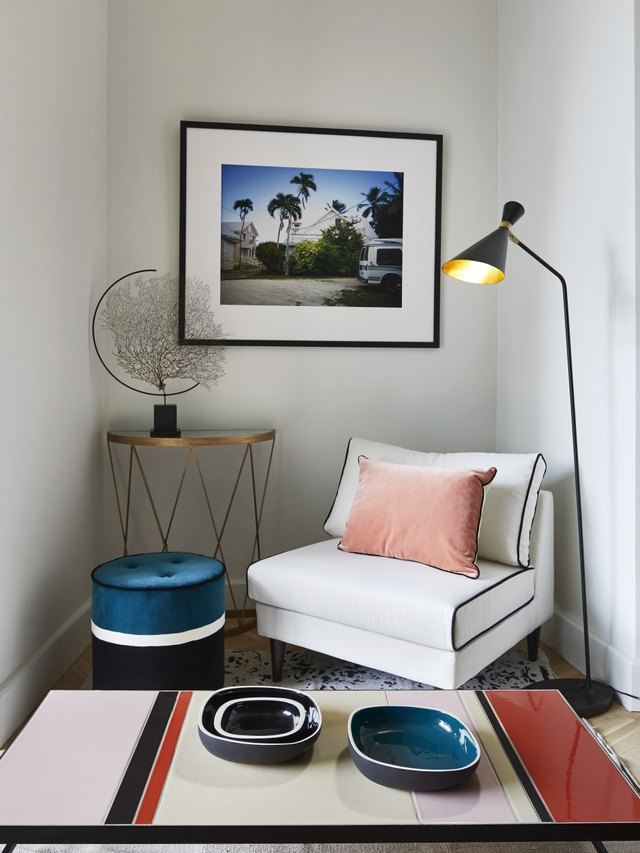 A lounge chair next to a side table with an avant garde globe