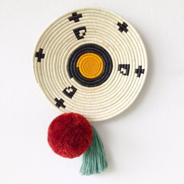 Round woven wall hanging with pom pom tassel