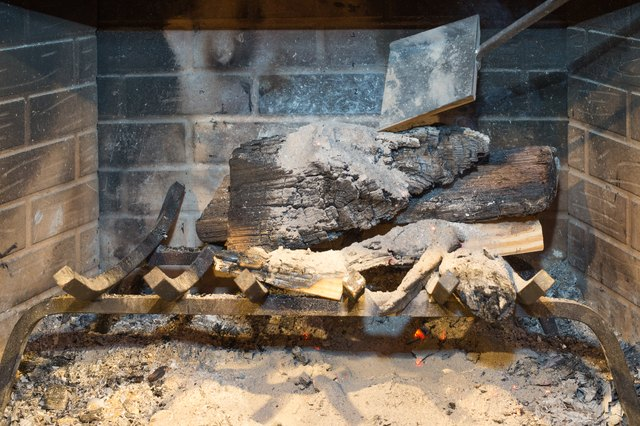 Scoop up the ash at the bottom of your fireplace with your fireplace shovel. Place it over the cooling wood and embers. Repeat this process slowly and ... & How to Put Out a Fire in a Fireplace | Hunker