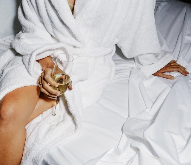 A woman in a bathrobe on a white bed with a glass of champagne in her hands.