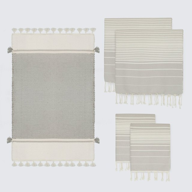 Set of towels and bathmat featuring neutral gray and cream design and subtle fringe
