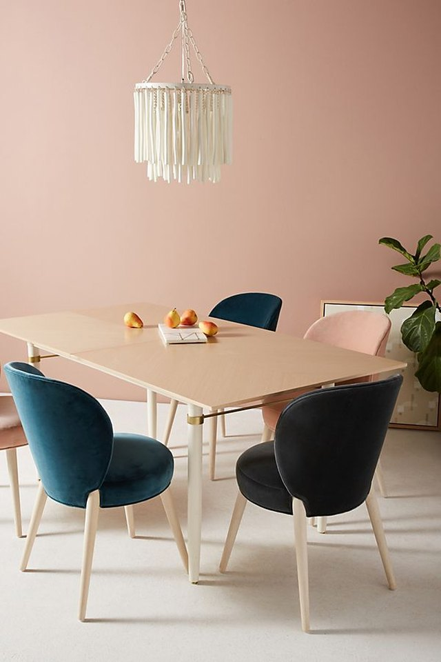 Four velvet dining chairs around a light-wood table with a pink wall.