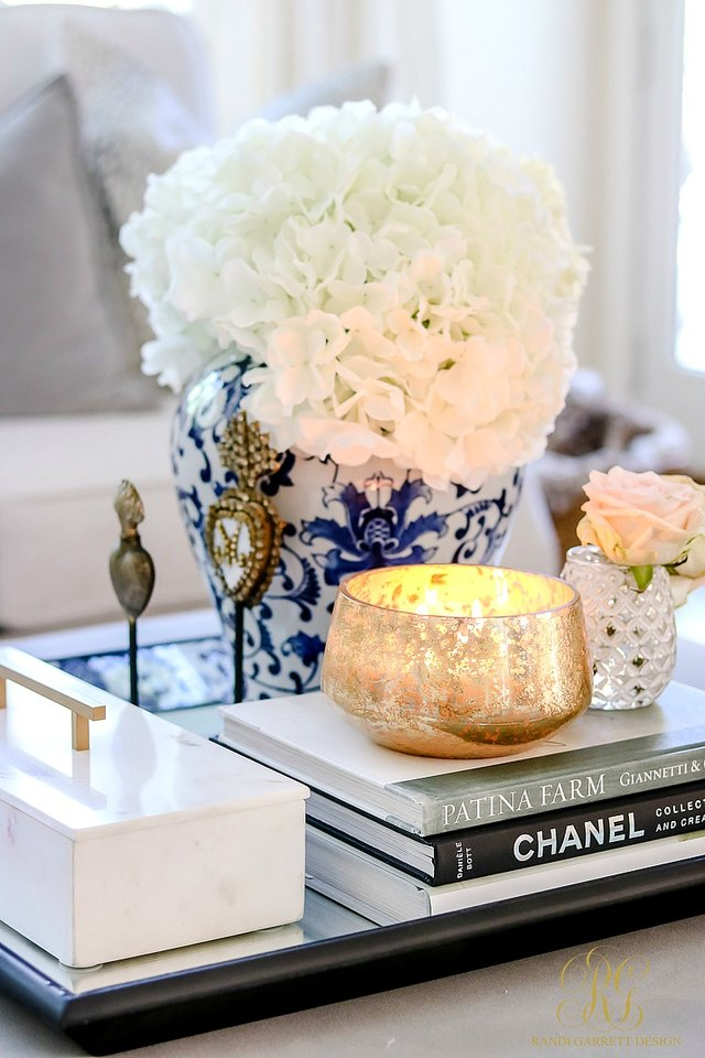 Close-up of coffee table vignette with white flowers in blue vase, candle, and decorative books