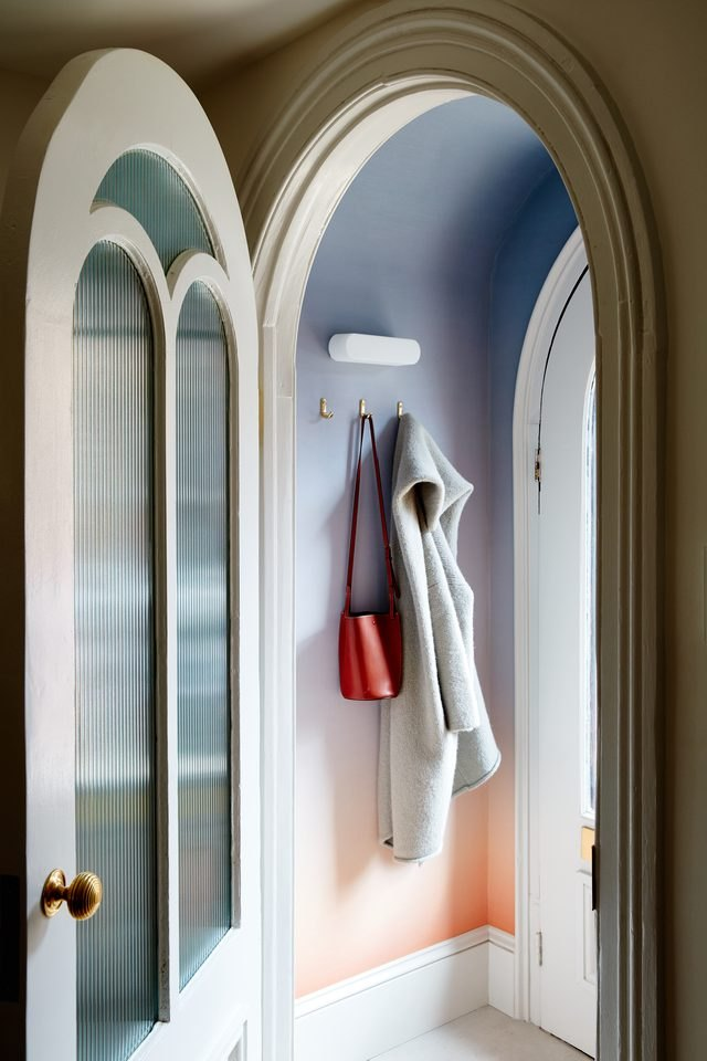 Ombre walls in a round entryway with a coat and purse hanging from hooks