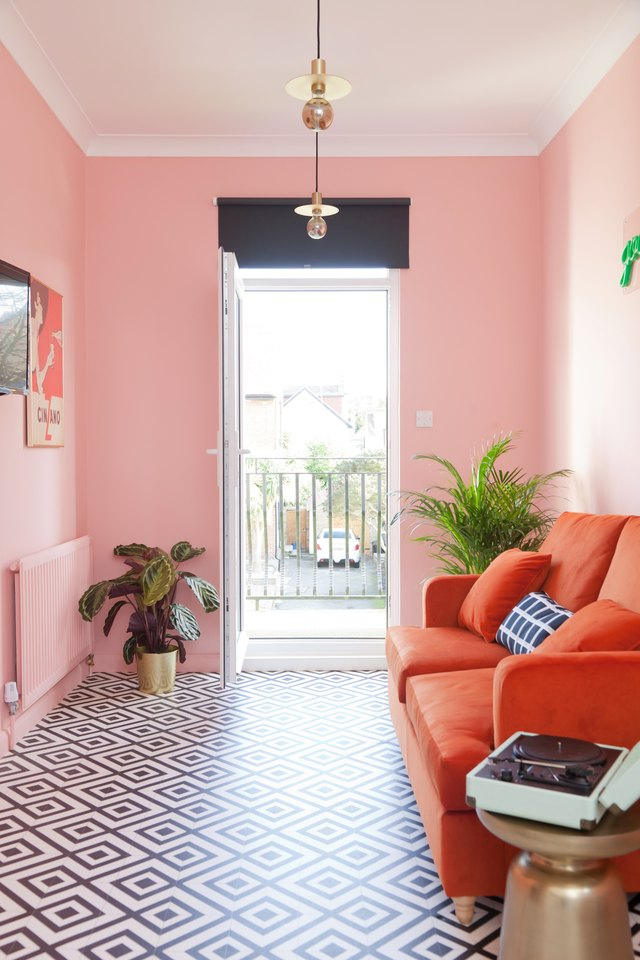 pink living room with red velvet sofa