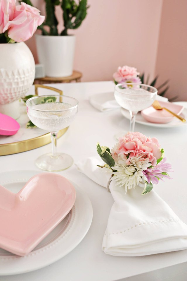 Soft-pink heart plates on a white tablecloth with floral napkin rings.