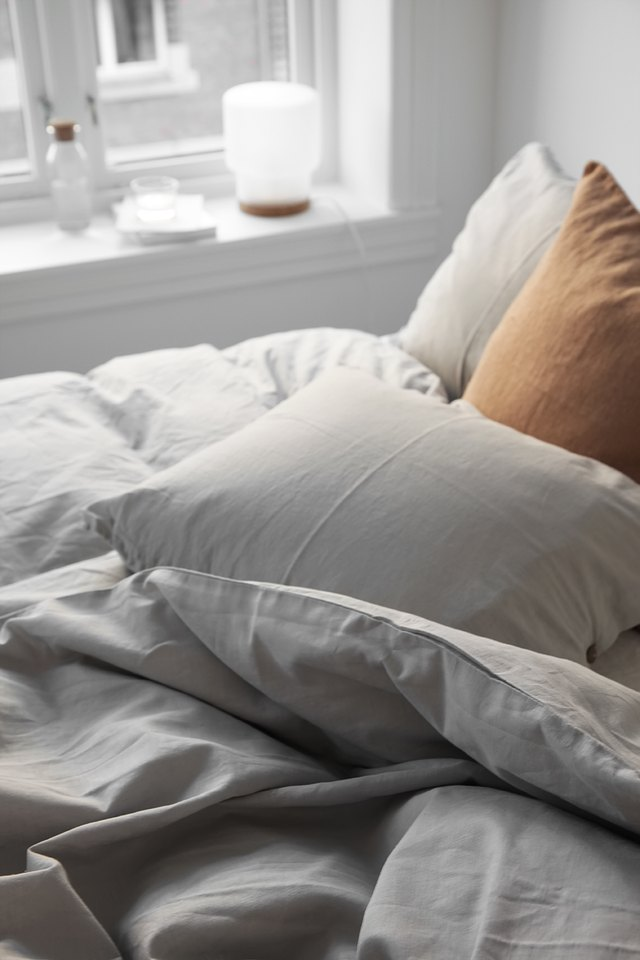A wrinkled white duvet and a tan pillow.
