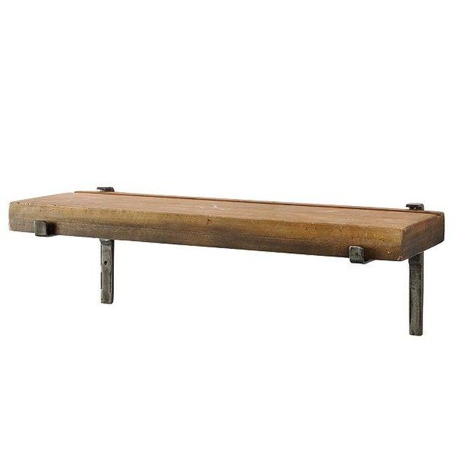 Floating wooden shelf with black metal brackets