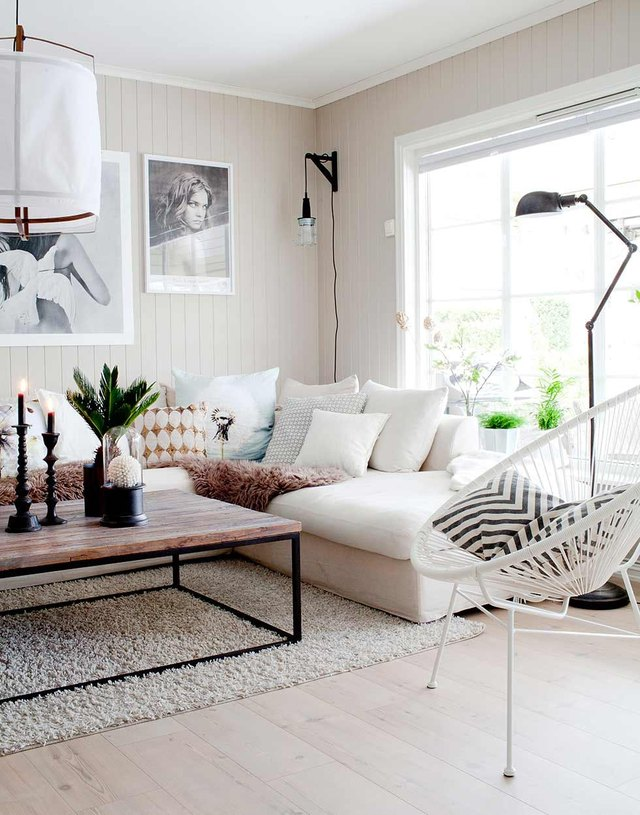 modern neutral toned living room white acapulco chair black and white geometric patterned throw pillows