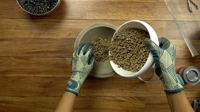 Adding gravel to DIY concrete fire bowl.