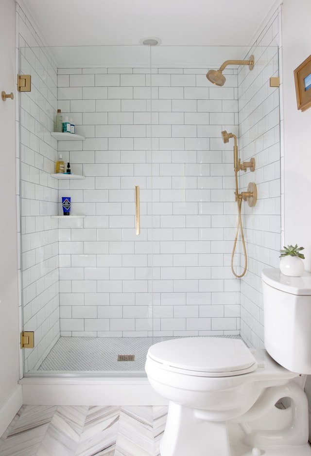 Photo of white tiled bathroom with glass walk-in shower.