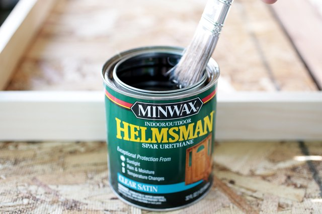 can of outdoor finish with paint brush in it.