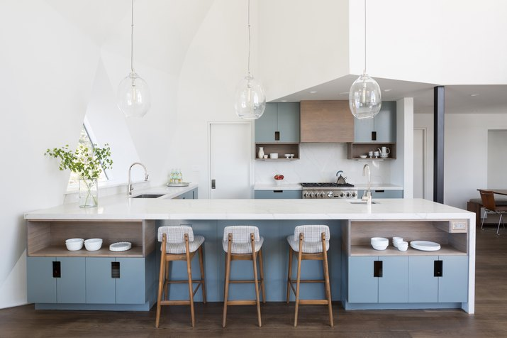 minimal kitchen with glass pendant lights and blue cabinets