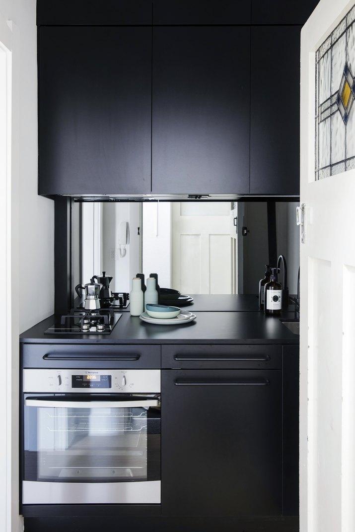 black kitchen cabinets with mirror backsplash