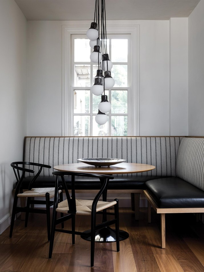 breakfast nook with banquette seating and clustered light fixture