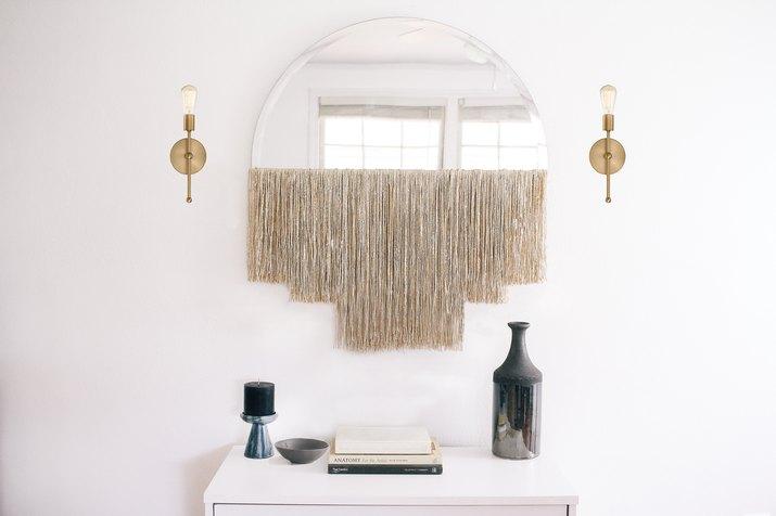 White fringe fringe mirror with gold sconces over dresser with vase