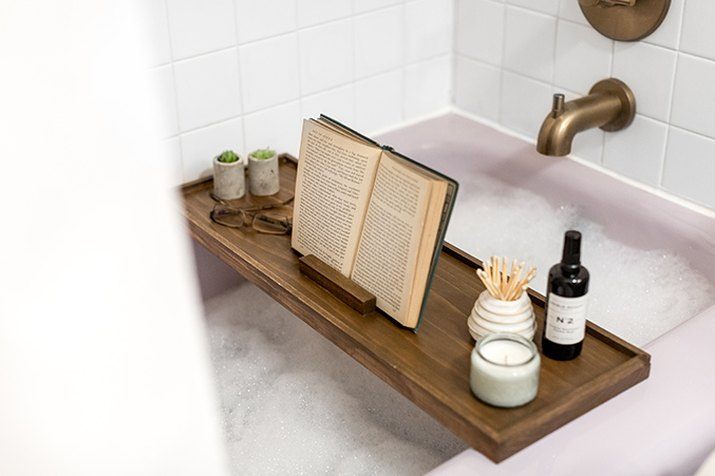Wood bath tray with reading glasses, book, and plants over bathtub