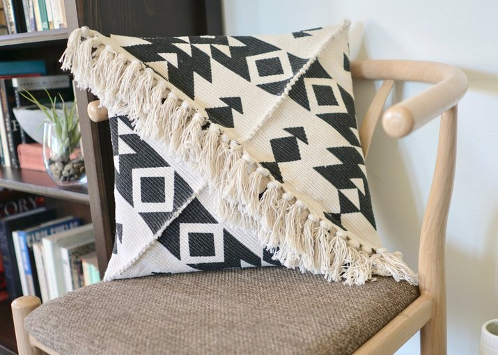 Black and white fringed pillow on chair next to bookcase