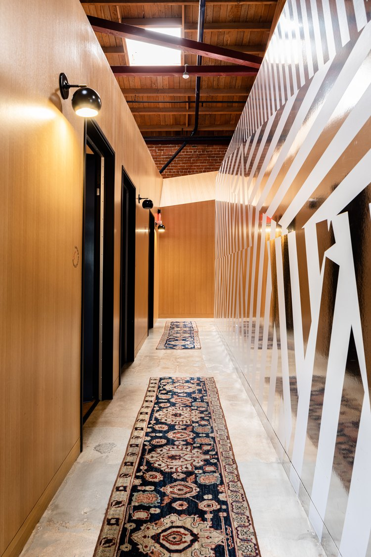 Long hallway with wood and wallpapered walls and Persian style runner