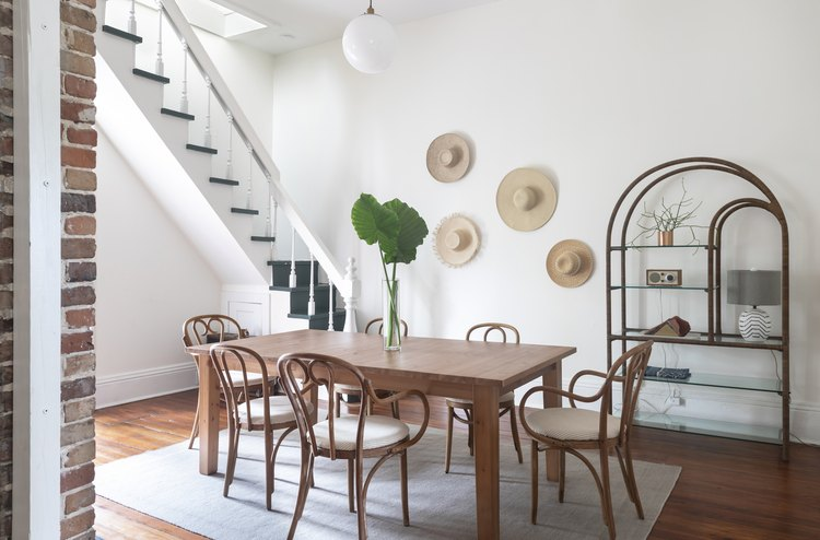 Dining room with wood table and hanging straw hats on wall